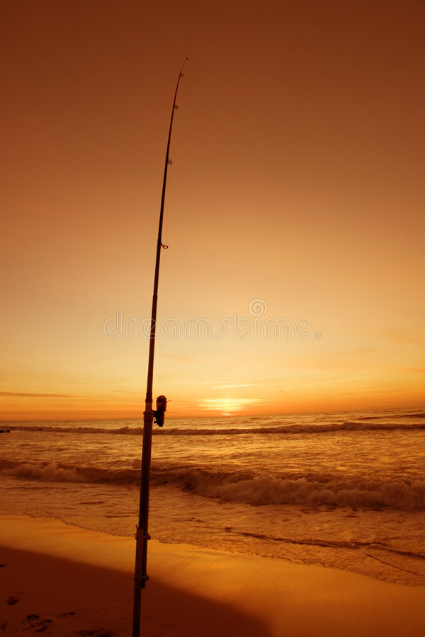 Fishing Pole. A fishing pole stuck in the sand at sunset royalty free stock photos