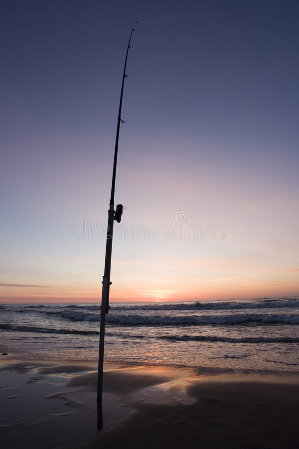 Fishing Pole. A fishing pole stuck in the sand at sunset stock photography
