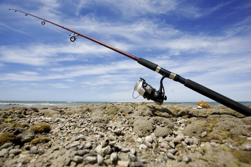 Fishing Pole. A fishing pole sticking out of the ocean coral reef stock photo