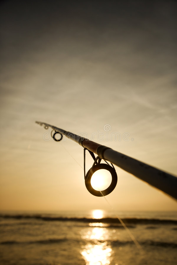 Fishing pole against ocean. At sunset royalty free stock image