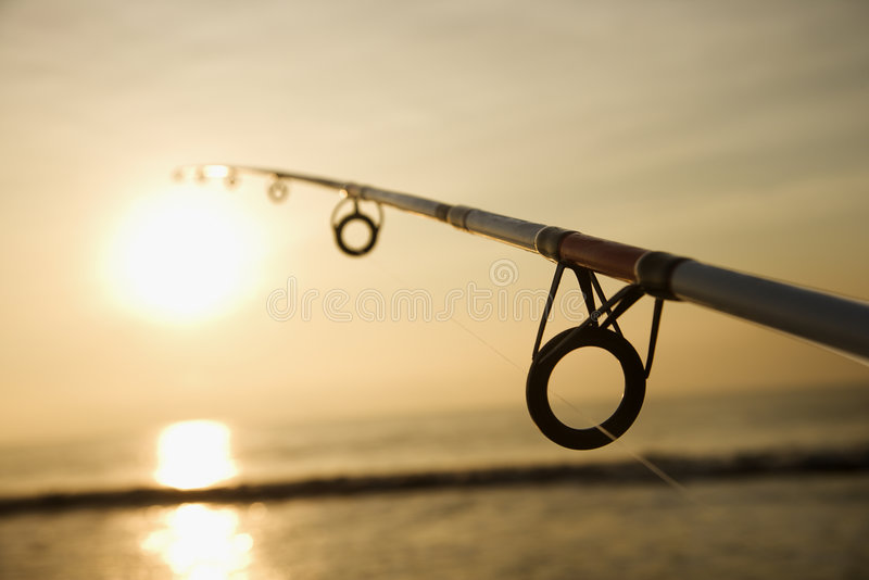 Fishing pole on beach. Fishing pole against ocean at sunset stock photos
