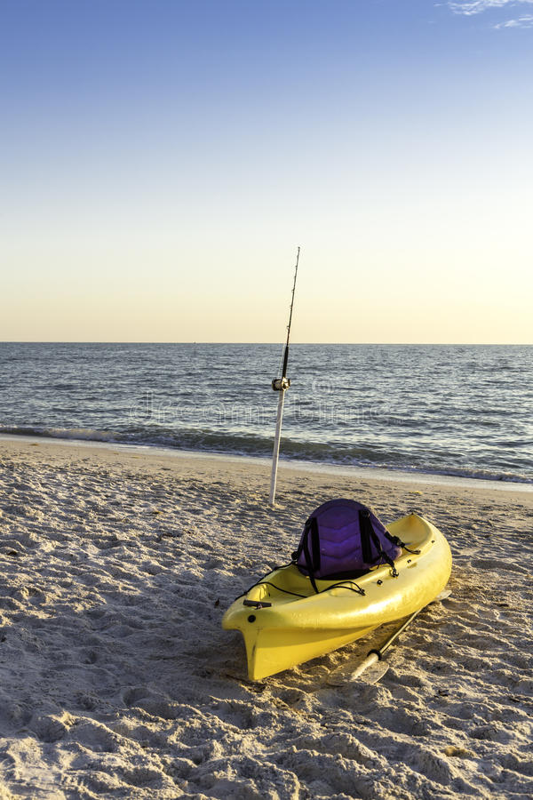 Fishing pole and canoe on the beach royalty free stock images
