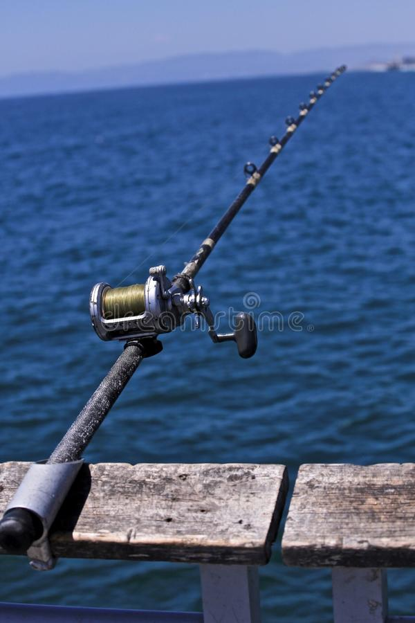 Fishing pole. Following the leading line of a fishing pole takes you off the pier to the big blue ocean in California royalty free stock images