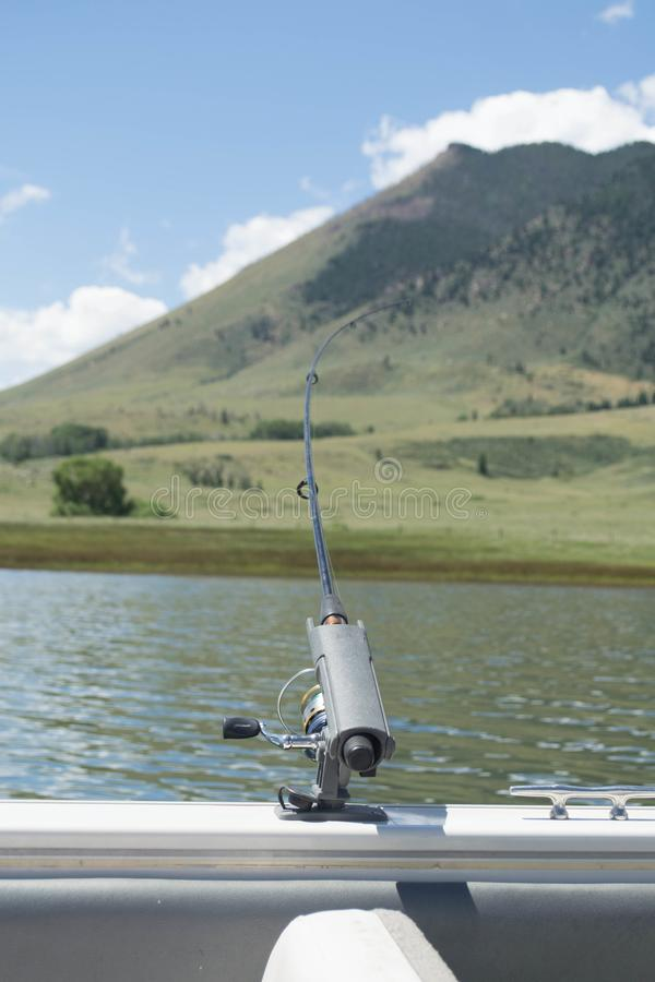 A fishing pole in holder on a boat. A fishing pole in a holding on a boat slightly bending with mountain in the background, Lake Hattie, Sheep Mountain, Laramie royalty free stock photography