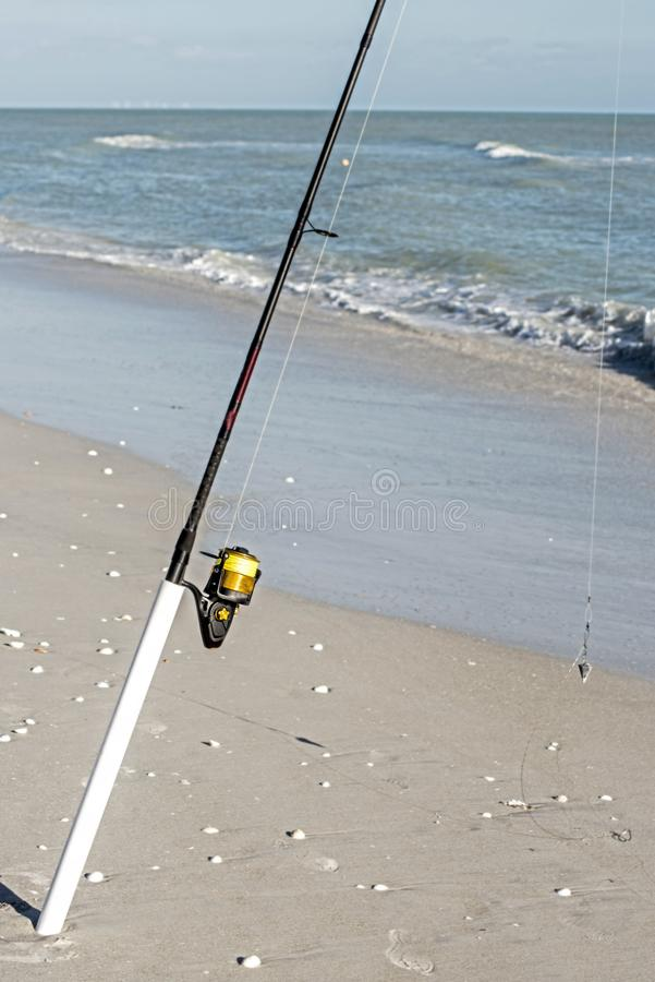 A fishing pole with line sits on the beach ready. stock image