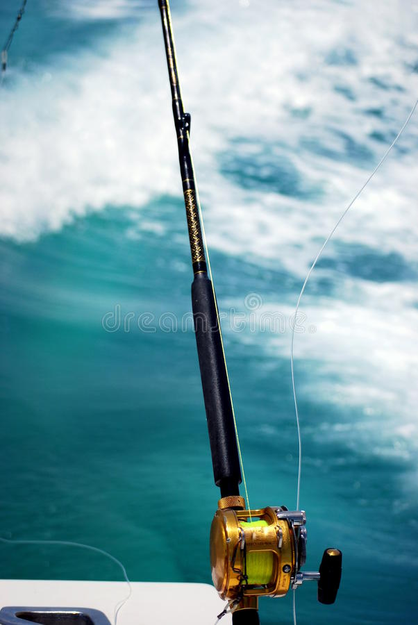 Fishing pole over the water. A fishing pole in a rod holder over the water as the boat is moving and the line is blowing in wind and the wake shows in the blue stock photo