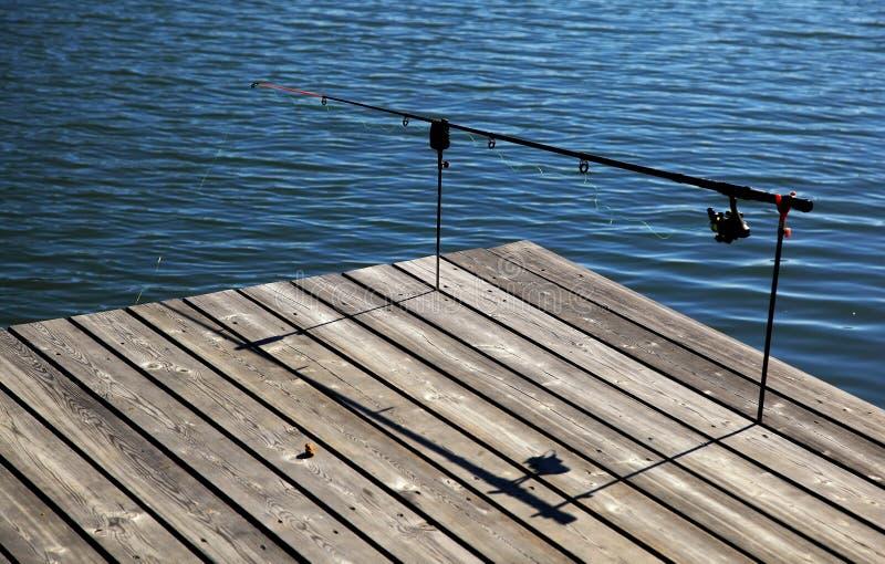 Fishing pole on pier. One fishing pole on pier stock image