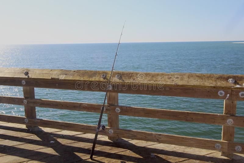 Fishing pole on the pier. One fishing pole leaning on the pier royalty free stock image