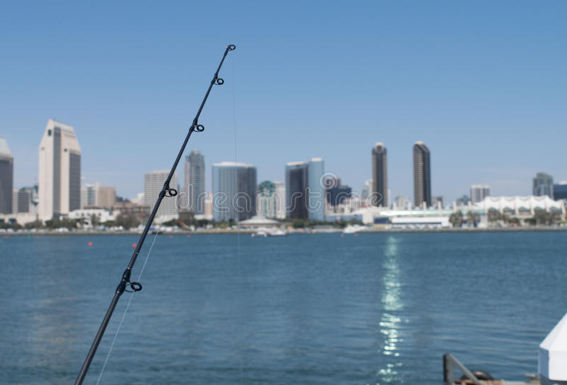 Fishing pole with San Diego skyline and harbor in background. View of San Diego harbor and architecture from fishing dock Coronado Island royalty free stock photography