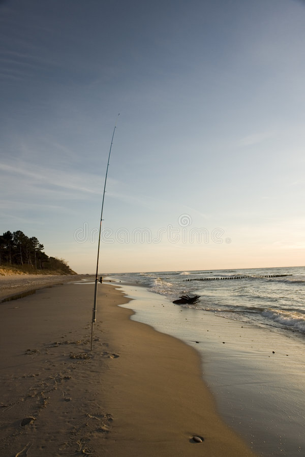 Fishing pole in sand on beach stock photography
