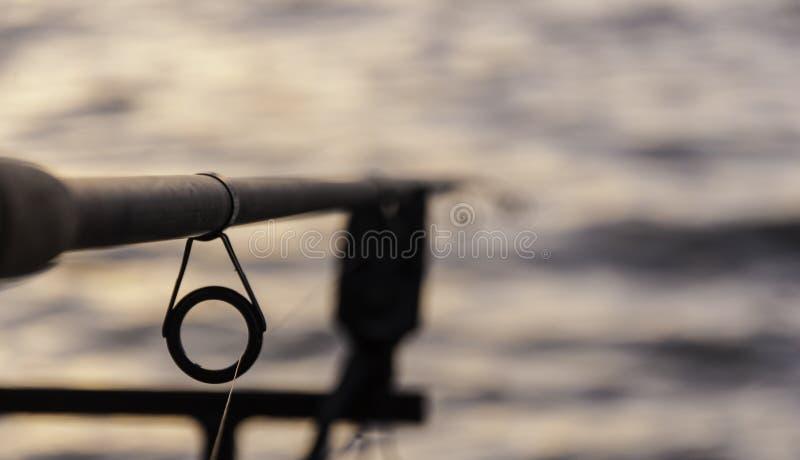 Fishing pole at sunset. Fishing, fishing pole, sunset beach sea stock photo