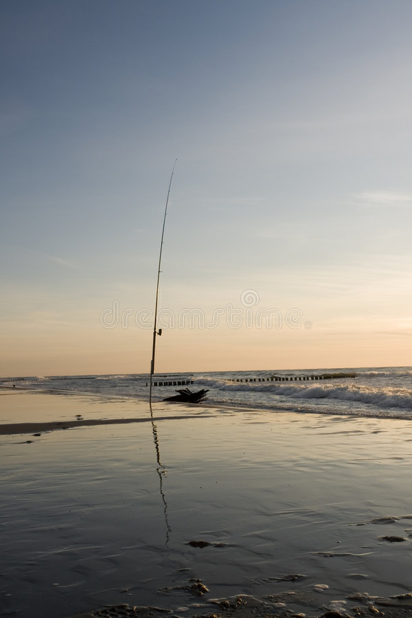 Fishing pole at water's edge royalty free stock images