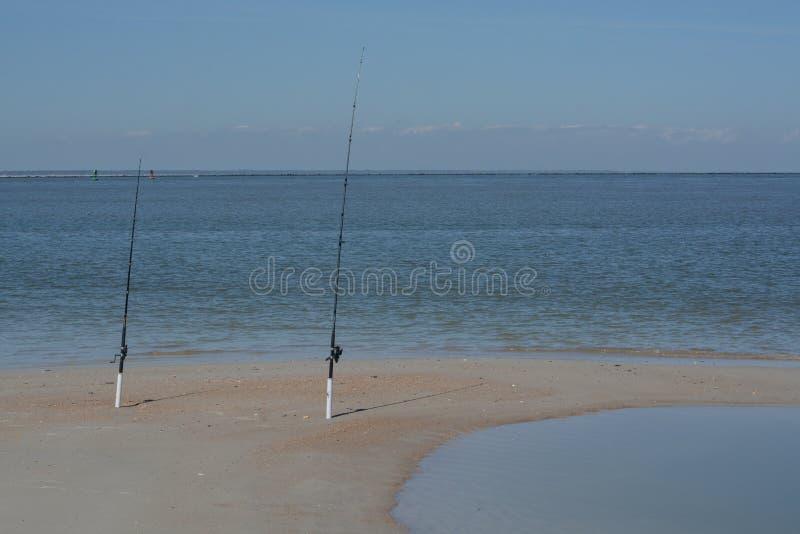 Fishing poles on Fernandina Beach, Cumberland Sound, Fort Clinch State Park, Nassau County, Florida USA.  stock photos