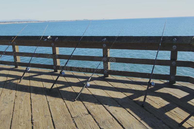 Fishing poles on the pier stock photography