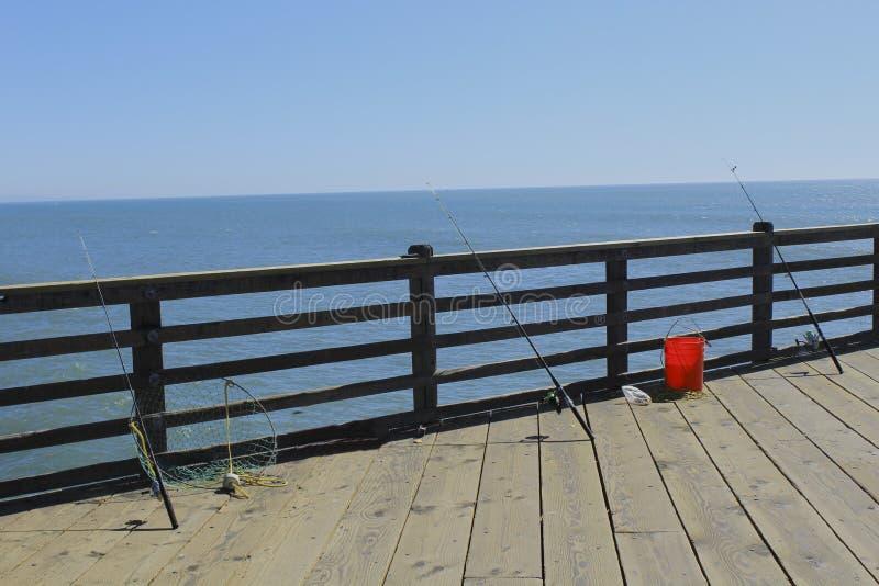 Fishing poles on the pier stock photo