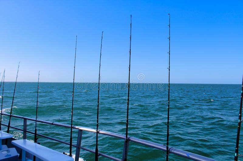 Fishing poles on the ocean royalty free stock photo