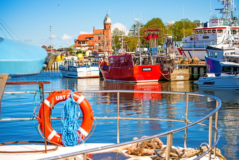 Fishing port of Ustka, Poland with old lighthouse. And fishing cutters royalty free stock images