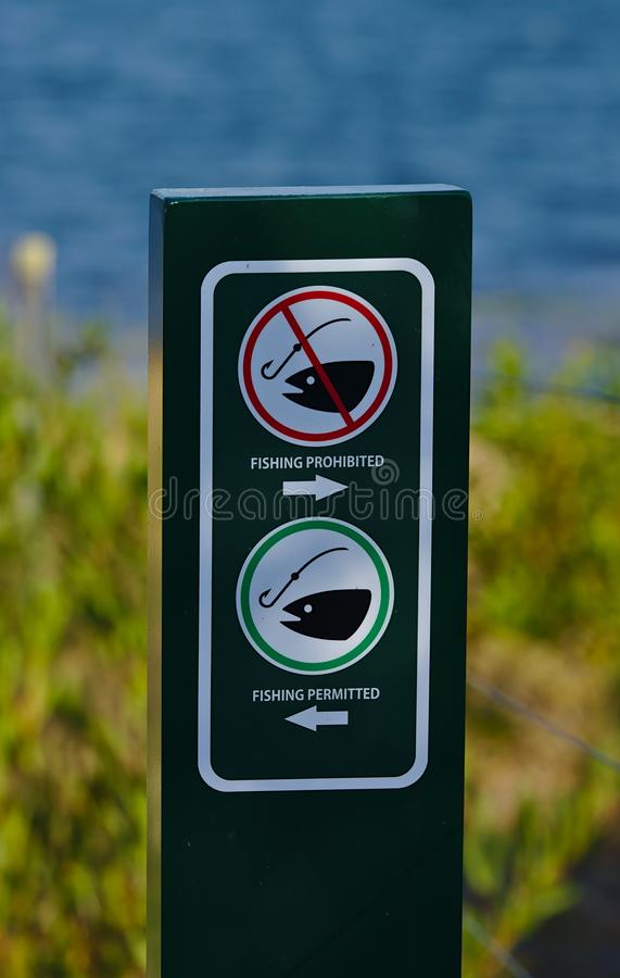 Fishing prohibited and Fishing permitted sign stock photography