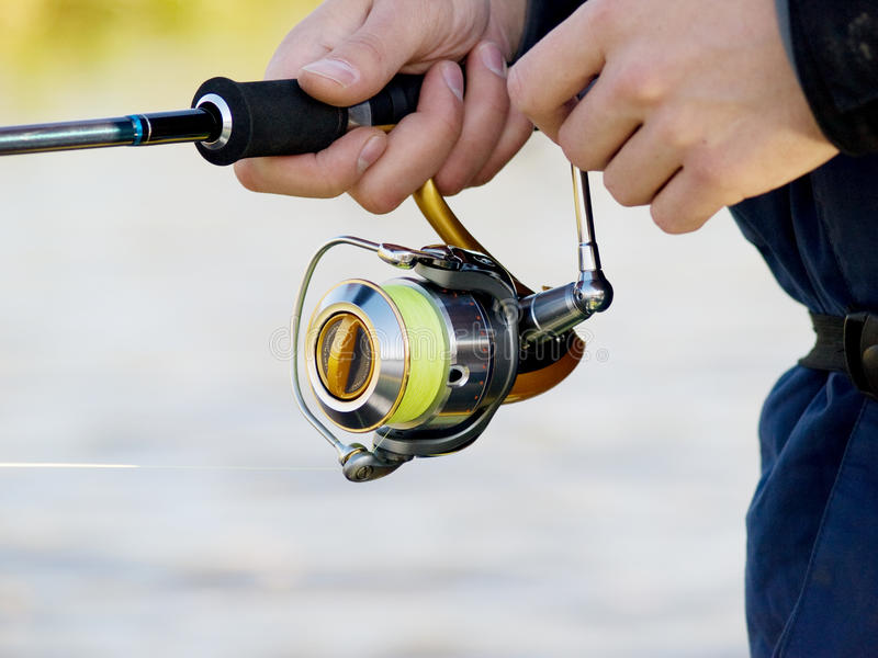Fishing reel. The fisherman with a fishing reel royalty free stock image