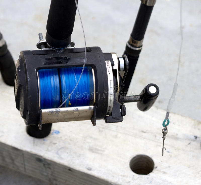 Fishing reel. Black and Silver fishing reel in a rod holder stock photo