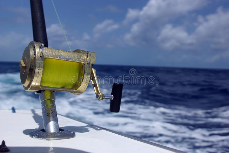 Fishing reel. A bronze fishing reel and rod setup at sea stock image