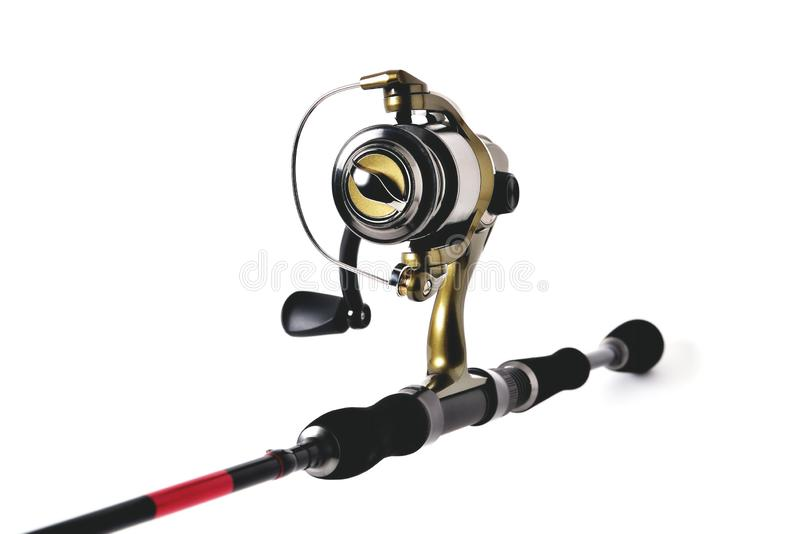 Fishing reel on a fishing rod, white background close-up. Copy space royalty free stock image