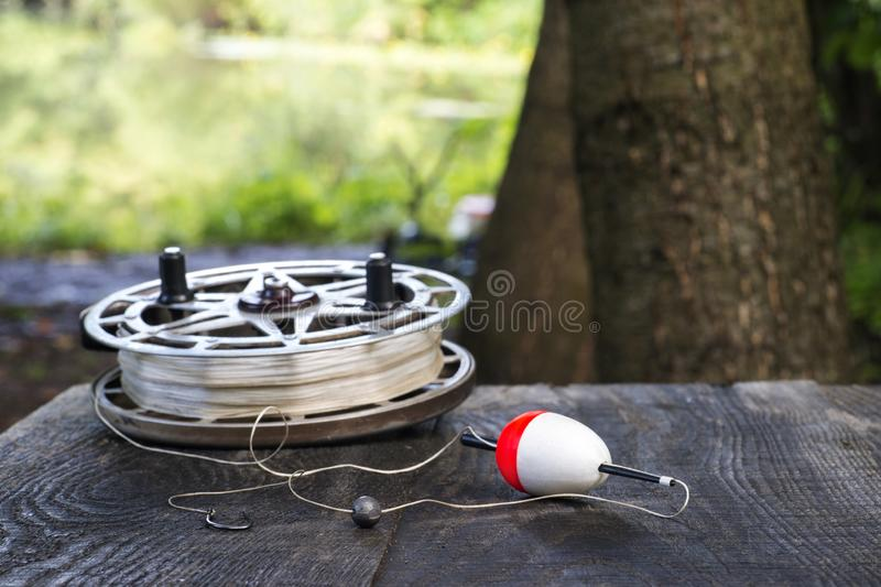 Fishing reel with fishing line, red and white float, hook and sinker on wooden table on natural background. The concept of classic fishing tackle. Text space stock photography