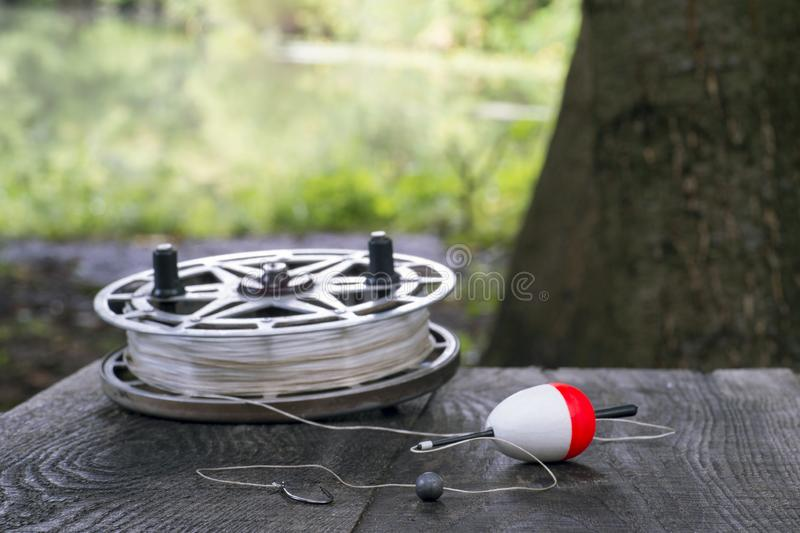 Fishing reel with fishing line, red and white float, hook and sinker on wooden table on natural background. The concept of classic fishing tackle. Text space royalty free stock photos