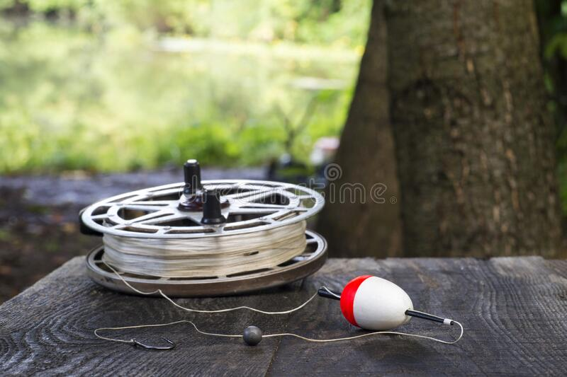 Fishing reel with fishing line, red and white float, hook and sinker on wooden table on natural background. The concept of classic fishing tackle. Text space royalty free stock photography