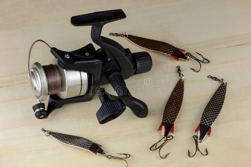 Fishing Reel and Fishing Lures on a Wooden Surface royalty free stock photo