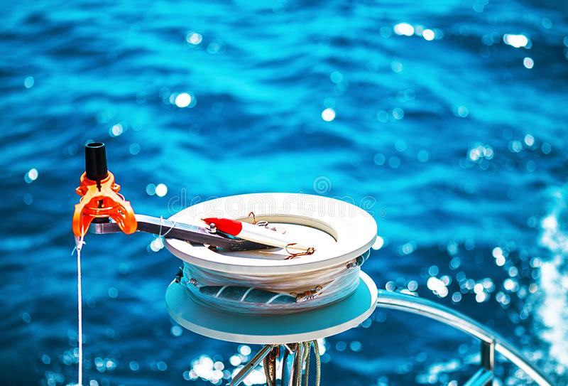 Fishing reel or rod reel, rod. Sailing yacht catamaran in the sea in Greece, turquoise waters of Aegean Sea near Athens. Famous travel sailing destination in royalty free stock photos