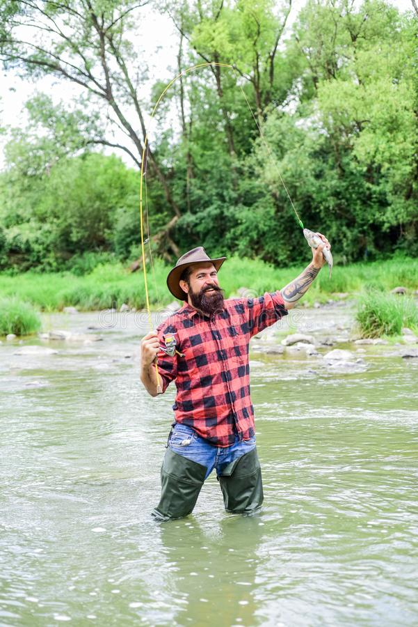 Fishing requires you to be mindful and fully present in moment. Fish on hook. Fishing masculine hobby. Brutal man wear. Rubber boots stand in river water royalty free stock image