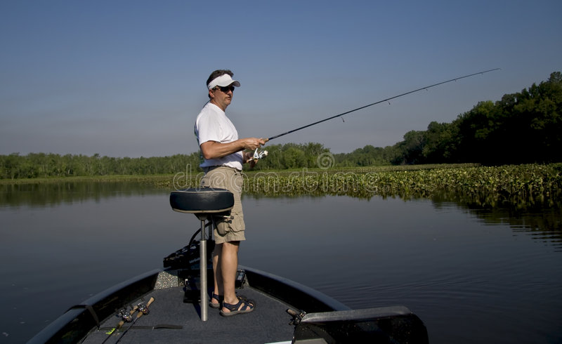 Fishing in the river. Man fishing in a river off the end of his bass boat royalty free stock photo