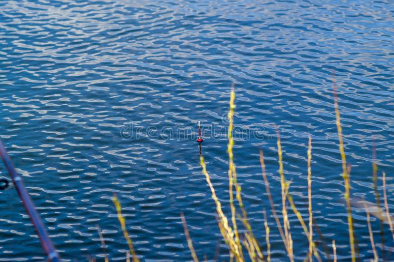 Fishing on a river with blue water. Red float and fishing pole. Red float and fishing pole. Fishing on a river with blue water royalty free stock images