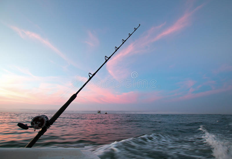 Fishing road on charter fishing boat against pink sunrise sky on the Sea of Cortes in Baja Mexico royalty free stock images