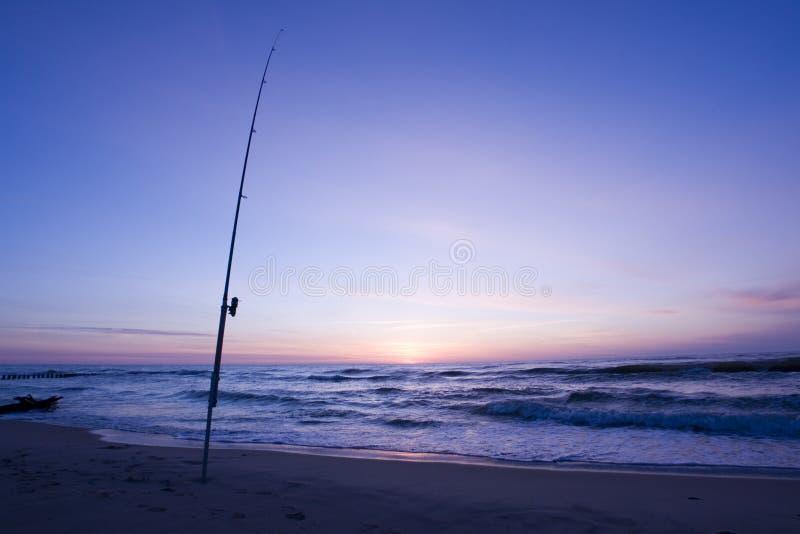 Fishing rod on the beach stock image