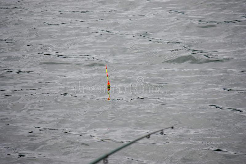 A fishing rod, a fishing rod with a cork or a float on a line in a lake. Close-up. A fishing rod is out of focus stock images