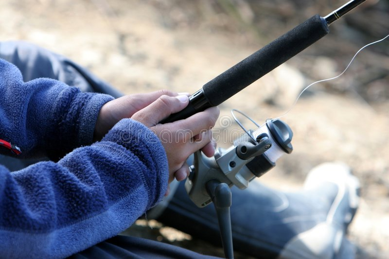 Fishing Rod and Reel. Close up of fishing rod and reel in hands royalty free stock photography