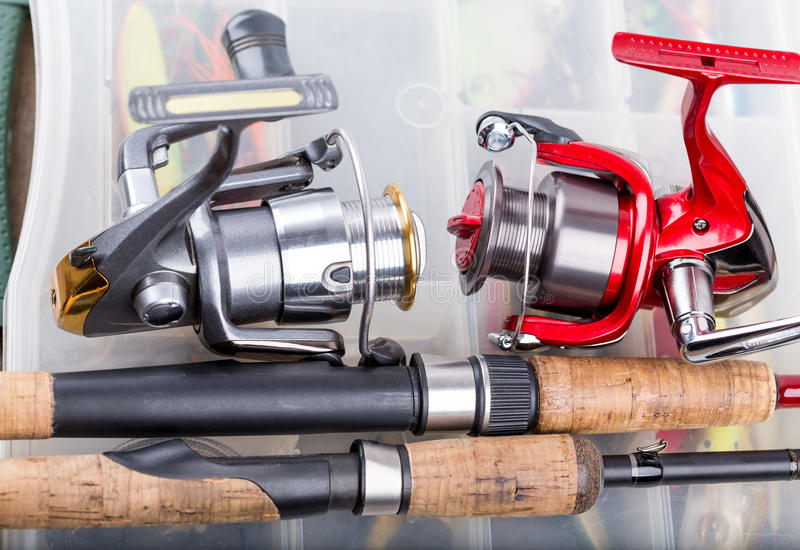Fishing rod with reel on background of tackles in boxes. Closeup fishing rod with reel on background of tackles in boxes with baits, lure, wobblers stock image