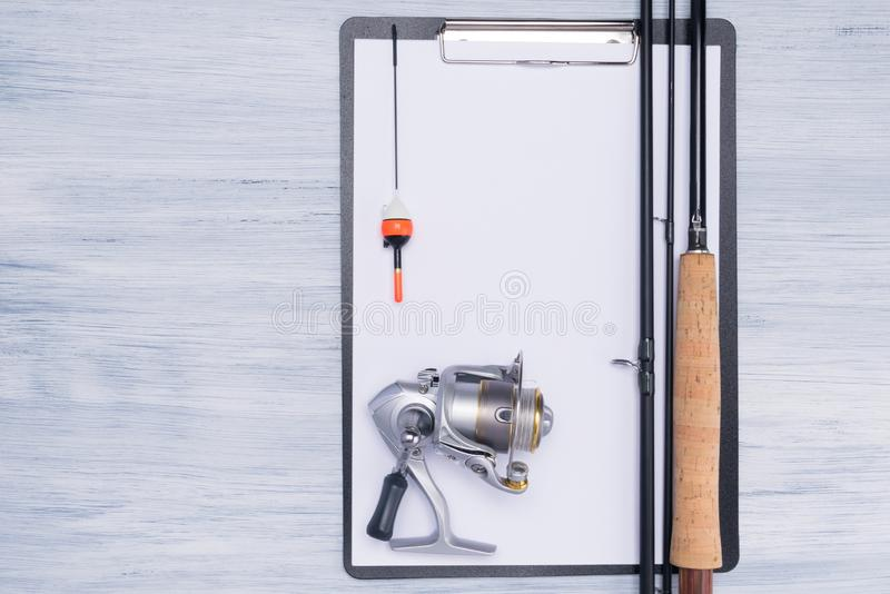 Fishing rod with reel for fishing and a clean tablet for notes on a light background. Fishing rod with reel for  fishing and a clean tablet for notes on a light royalty free stock photo