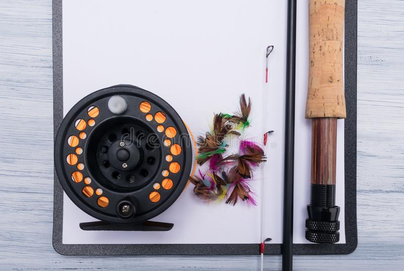 Fishing rod with reel are on a tablet with clean paper stock photography