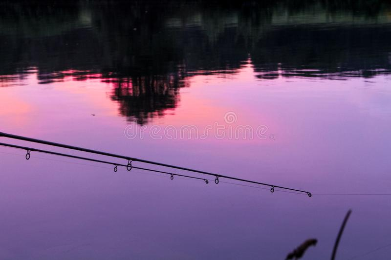 Fishing rod reflexing sunset in a river. stock image