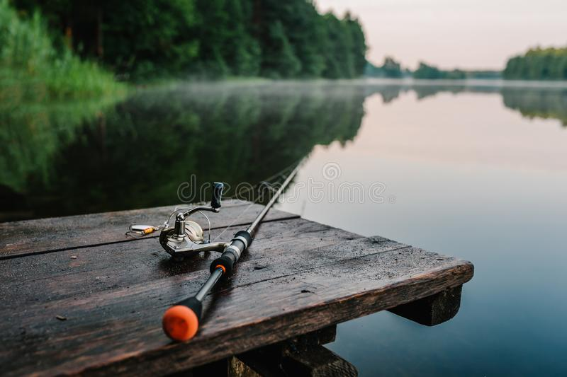 Fishing rod, spinning reel on the background pier river bank. Sunrise. Fog against the backdrop of lake. Misty morning. wild royalty free stock photography