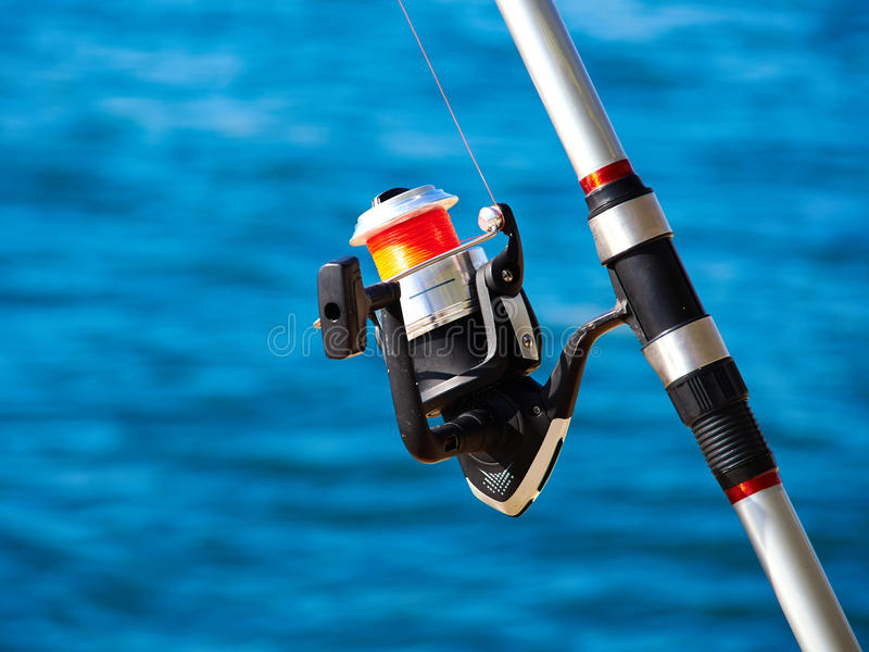 Fishing rod with a spinning reel. With sea beach ocean background royalty free stock photography