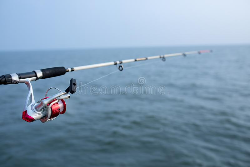 Fishing rod and spinning reel and sea water background royalty free stock photo
