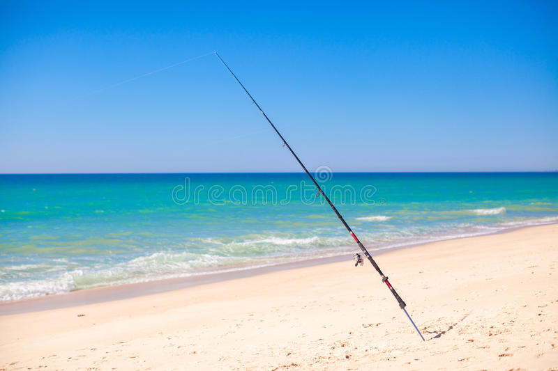 Download Fishing Rod In White Sand On Tropical Beach, Stock Photo - Image: 35608710