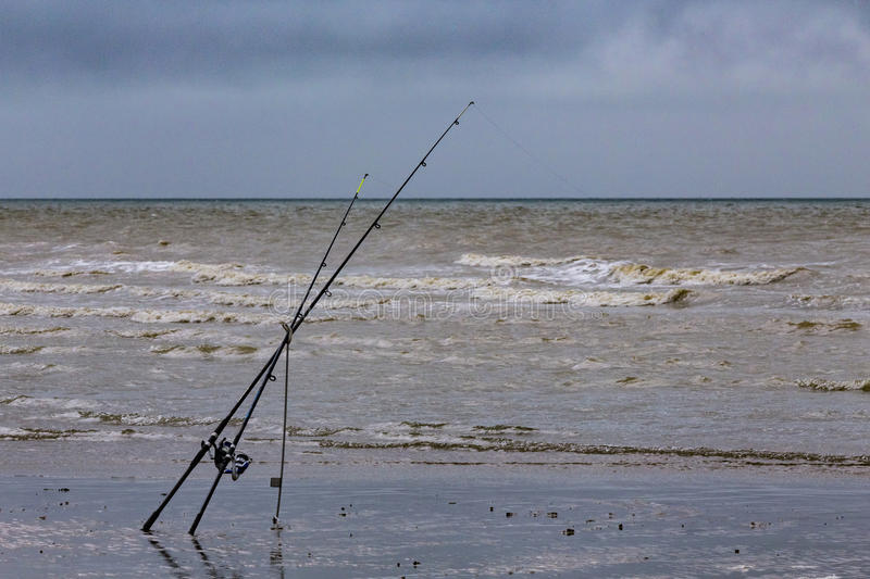 Fishing rods on the beach royalty free stock image