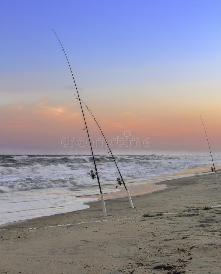 Fishing rods on Cutter Banks, NC. Fishing rods on empty sandy beach on Cutter Banks, North Carolina, USA at sunset stock photography