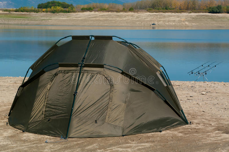 Fishing rods with reels on a support system rod pod and tourist tent the holiday camp on the bank. stock photo