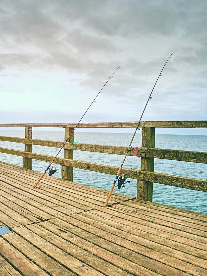 Fishing on sea bridge. Fishers rods against the wooden handrail of the beach mole. Overcast day, with the hidden sun royalty free stock photo